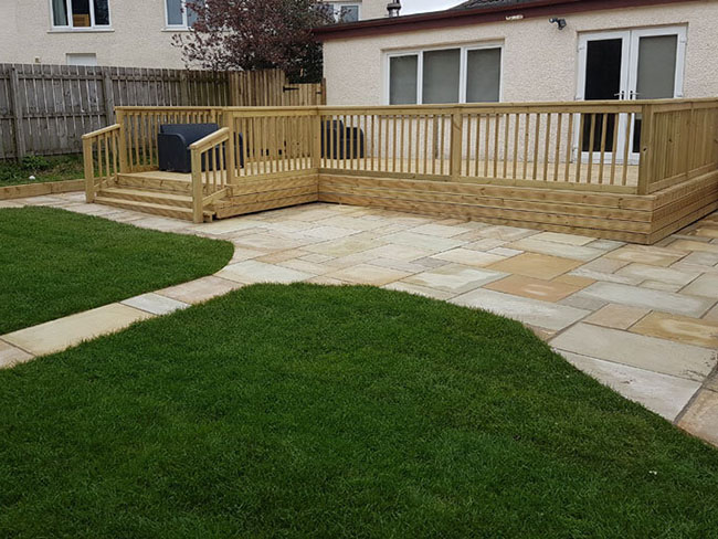 Artificial grass Glasgow showing decking and Indian Sandstone patio