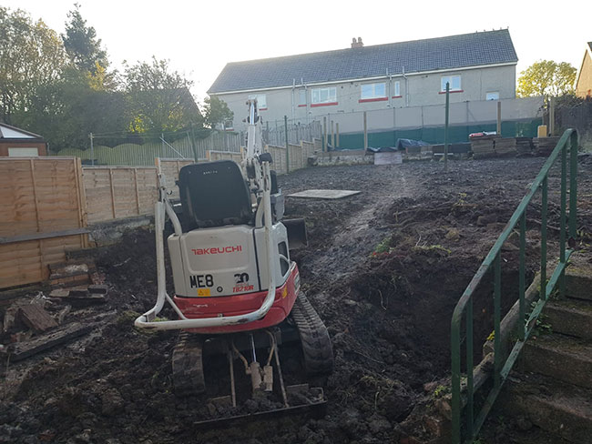 Mini digger in garden on Peat Road in Pollock.