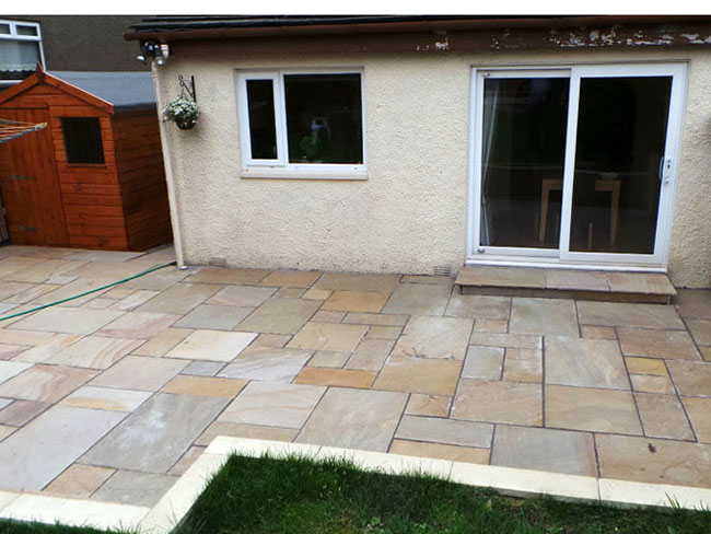 Indian sandstone garden patio with fencing & retaining wall